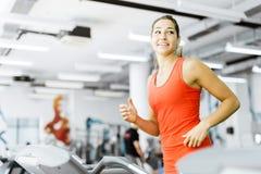 跑在健身房的一辆踏车的美丽的少妇 免版税库存照片