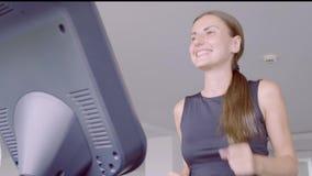 跑在健身房的踏车的愉快的微笑的妇女在健身俱乐部 影视素材