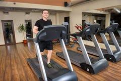 跑在健身房的踏车的年轻人 库存照片