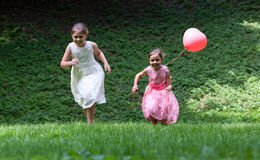 跑在公园的两个小女孩 免版税库存照片