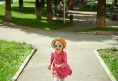 跑在公园的愉快的逗人喜爱的小女孩 幸福 免版税库存照片