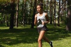 跑在公园的运动的妇女 图库摄影