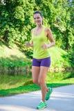 跑在公园的年轻美丽的运动的亭亭玉立的妇女 图库摄影