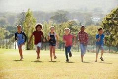 跑在公园,正面图的六个青春期前的朋友 免版税库存图片