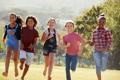 跑在公园,正面图,关闭的六个青春期前的朋友  库存照片