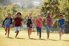 跑在公园,正面图,关闭的六个青春期前的朋友  免版税库存图片