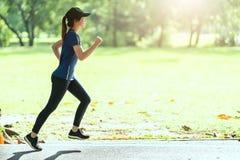 跑在公开自然城市公园的年轻可爱的愉快的亚裔赛跑者妇女穿有拷贝空间和太阳lig的运动的运动服 库存图片