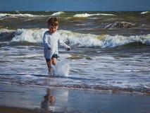 跑在兴高采烈的波浪的大字书写的热心男孩 Impre 库存图片