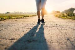 跑在农村路的年轻运动的健身妇女足迹在夏天 免版税库存图片