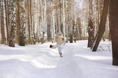 跑在冬天森林的逗人喜爱的矮小的愉快的女孩 免版税库存图片