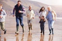 跑在冬天海滩的多一代家庭 库存图片