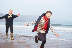 跑在冬天海滩的祖父和孙子 免版税图库摄影