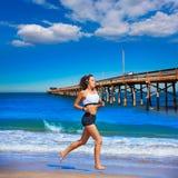 跑在加利福尼亚海滩的美丽的深色的女孩 免版税库存图片