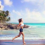 跑在加勒比海滩的美丽的深色的女孩 免版税库存图片