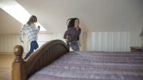 跑在台阶和跳在床上的三个俏丽的女孩为放松 影视素材