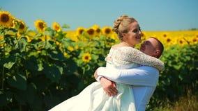 跑在向日葵的愉快的夫妇调遣,采取手和微笑 影视素材