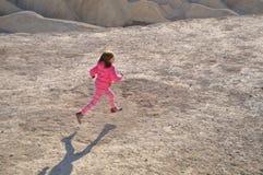 跑在土道路下的女孩 免版税库存照片
