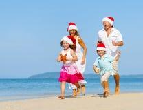 跑在圣诞节的海滩的家庭 免版税库存照片