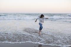 跑在在白色运动衫和牛仔裤地中海穿戴的岸的日落的被晒黑的青少年的女孩 库存照片