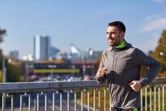 跑在城市桥梁的愉快的年轻人 免版税图库摄影