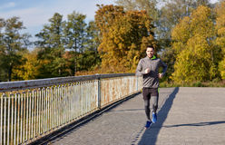 跑在城市桥梁的愉快的年轻人 免版税库存照片