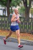跑在城市街道上的年长人在21 km距离ATB Dnipro马拉松期间 库存照片