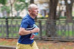 跑在城市街道上的老人在21 km距离ATB Dnipro马拉松期间 库存图片