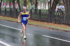 跑在城市街道上的老人在21 km距离ATB Dnipro马拉松期间 免版税库存照片