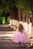 跑在夏天日落的庭院里我的一个被弄脏的小女孩 免版税库存图片