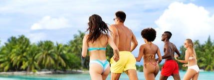 跑在夏天海滩的愉快的朋友 库存图片