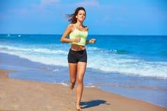跑在夏天海滩的美丽的深色的女孩 库存图片