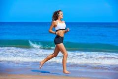 跑在夏天海滩的美丽的深色的女孩 免版税库存照片