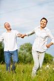 跑在夏天的愉快的资深夫妇 库存照片