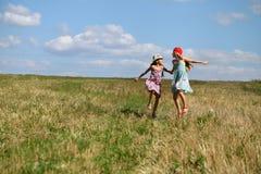 跑在夏天领域的两个小女孩 免版税库存图片