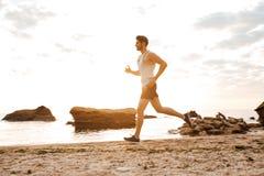 跑在多岩石的海滩的年轻运动的人运动员 免版税库存照片