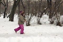跑在多雪的公园的孩子 免版税库存图片