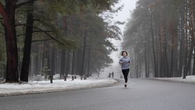 跑在多雪的公园的年轻可爱的白种人女孩在与耳机的冬天 前面静态射击 t 股票视频