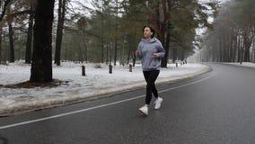 跑在多雪的公园的年轻可爱的白种人女孩在与耳机的冬天 r t 股票视频