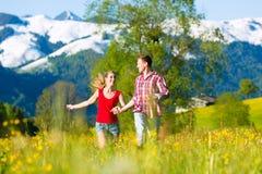 跑在有山的草甸的夫妇 库存图片
