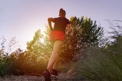 跑在山的妇女在日落 免版税库存照片