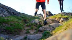 跑在山的岩石足迹的年轻夫妇早晨 有效的生活方式概念 免版税图库摄影