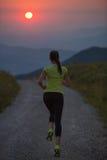 跑在山路的妇女在夏天日落 免版税库存照片
