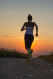 跑在山路的妇女在夏天日落 免版税库存图片
