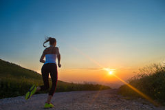 跑在山路的妇女在夏天日落 库存照片