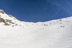 跑在山滑雪者的山坡 免版税库存图片