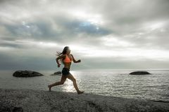 跑在岩石的妇女在Bakovern海滩,开普敦的日落 免版税库存照片