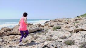 跑在岩石足迹的年轻运动的女孩穿桃红色服装 r 股票录像