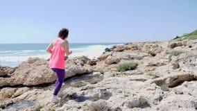 跑在岩石足迹的年轻运动的女孩穿桃红色服装 r t 影视素材