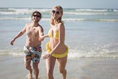 跑在岸的愉快的年轻夫妇在海滩` 库存图片