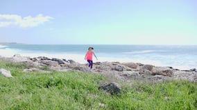 跑在往照相机的一串足迹的年轻人有动机的嬉戏妇女 背景的强的风雨如磐的海 影视素材